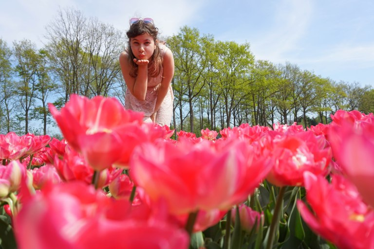 girl blowing a kiss at the camera with pink flowers in the foreground