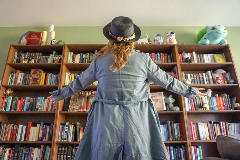 girl in long coat and hat standing in front of bookcase