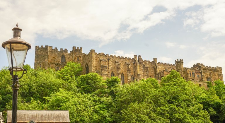 Durham castle with lightpost and trees
