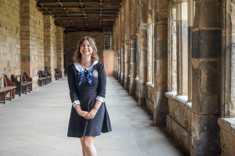 Excited girl in harry potter ravenclaw uniform in hogwarts film location durham castle hallway