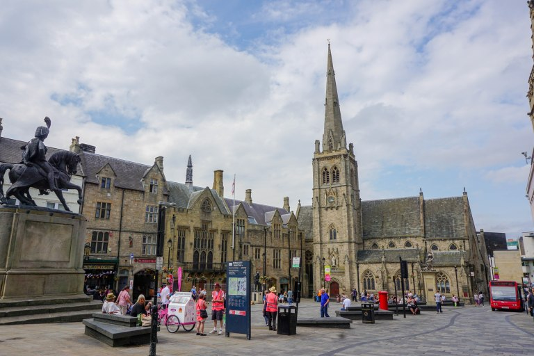 square in durham with church and statue