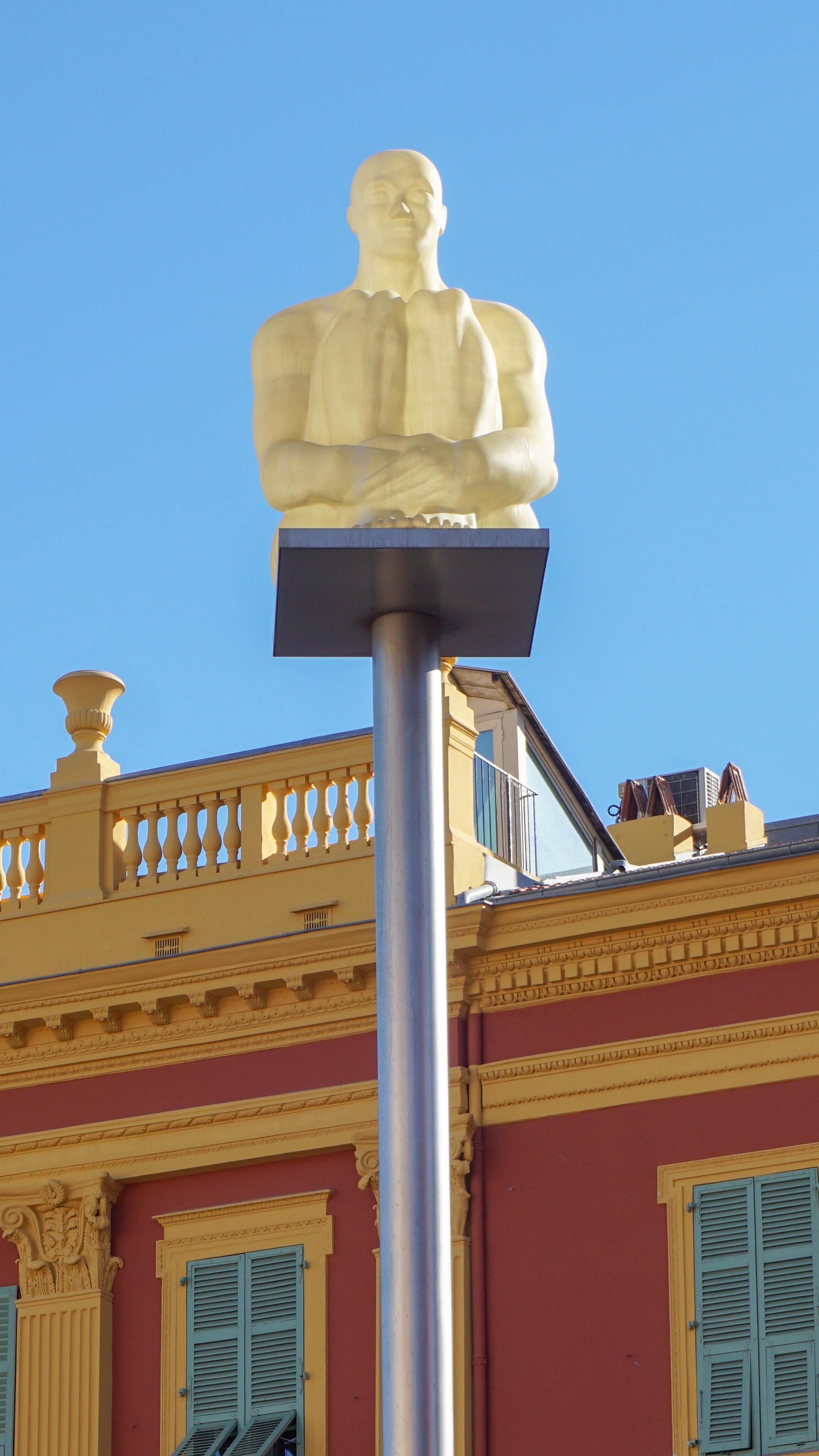 Glowing statue of a sitting man at Place Massena, Nice, France