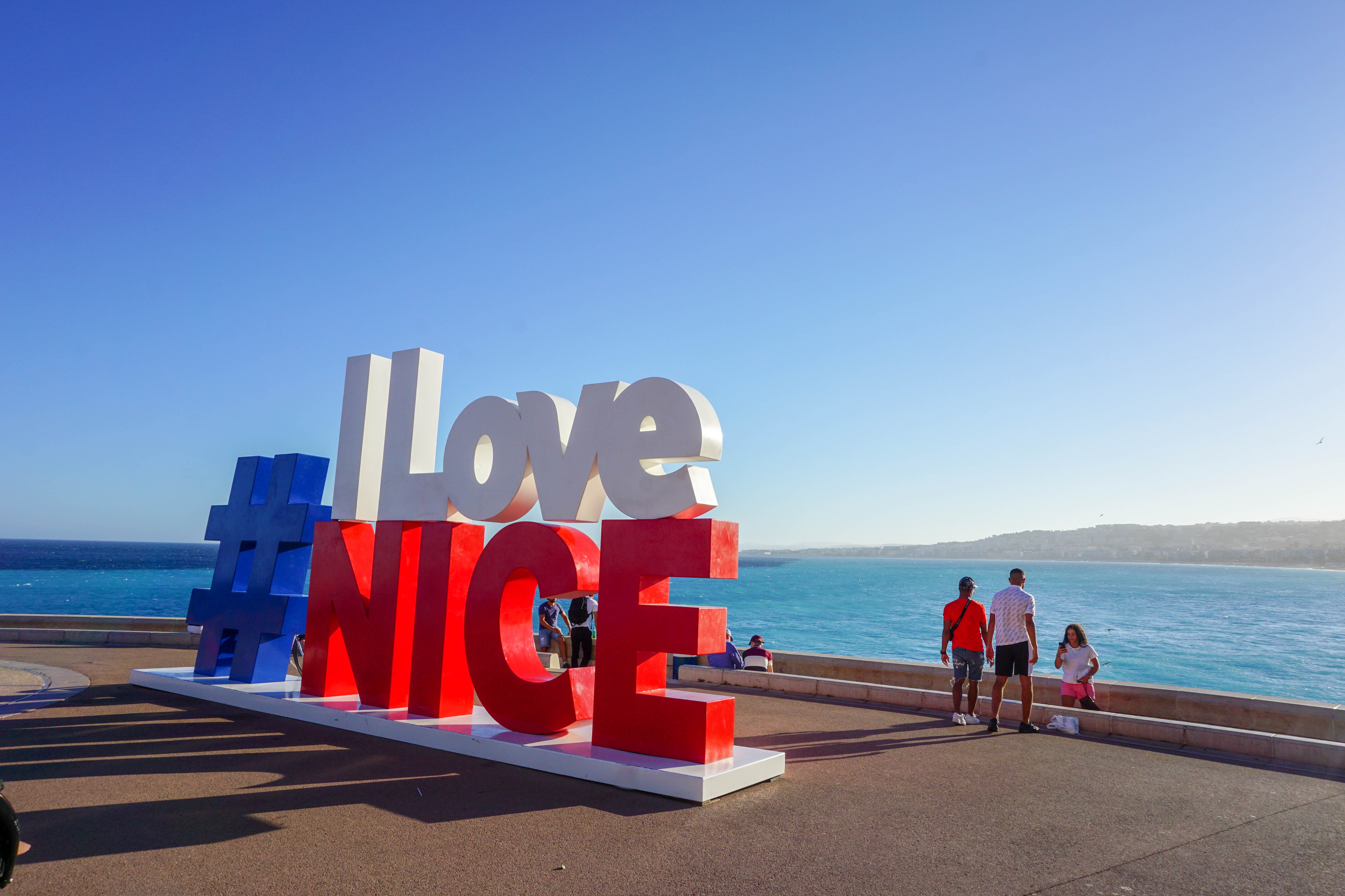 The #ILoveNice sign in city center Nice with blue sea in the background