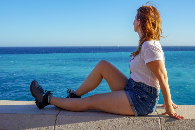 Girl overlooking the blue cote d'azur in Nice, France