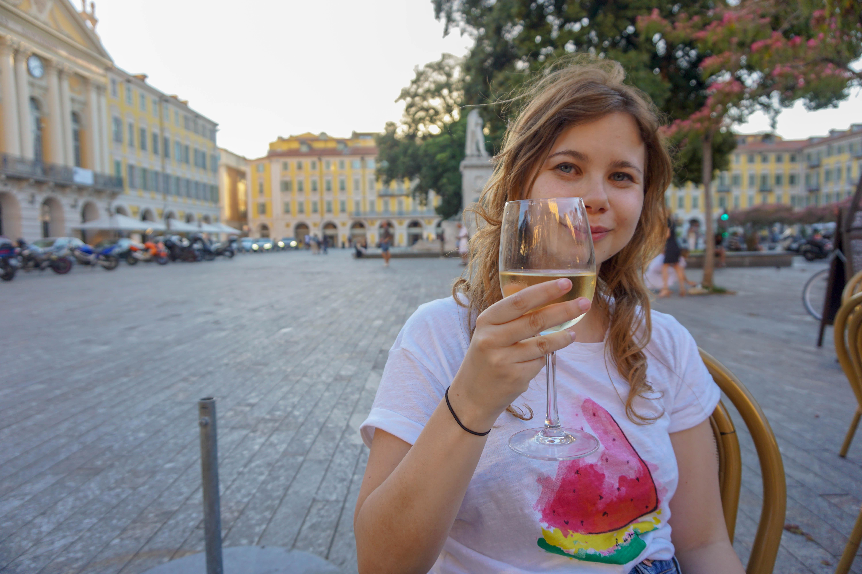 Girl drinking wine at Place Garibaldi in Nice, France